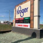 Kroger sign next to road with fuel center prices displaying electronically