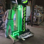Man in workshop testing neon sign for Supzilla Supplements and Nutrition Store