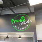 Fresh Eats Kitchen Neon Sign inside restaurant