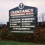 Illuminated Olentangy Professional Plaza sign with multiple businesses listed