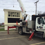 SignVision truck installing a large sign by the road for Capital Medical