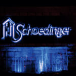 Shoedinger Funeral Home metal sign above fountain lit up in blue at night