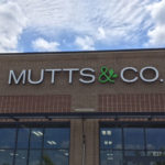 Mutts & Co sign on front of brick building with tall windows