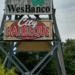WesBanco and City Barbeque signs on a metal tower