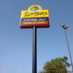 Tall Roosters Wings Restaurant sign next to road
