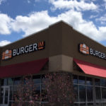Burger IM storefront with logo sign on two sides and red awnings