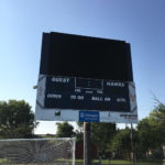 outdoor sign for high school sports field with soccer net and track in photo
