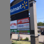 Walmart shopping center outdoor sign featuring multiple businesses