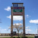 outdoor sign for a shopping center featuring multiple businesses