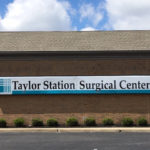 Brick building with a sign on the side for Taylor Station Surgical Center